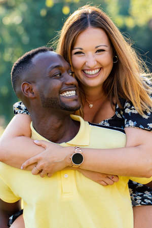 Close up outdoor portrait of happy multiracial couple doing piggybacking in park. Stok Fotoğraf - 153324627