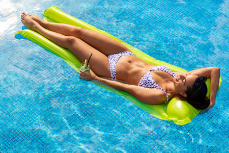 Full length top view portrait of attractive young woman enjoying cocktail on pool mattress. Girl in bikini on green plastic inflatable mattress in swimming pool. Stok Fotoğraf - 154068914