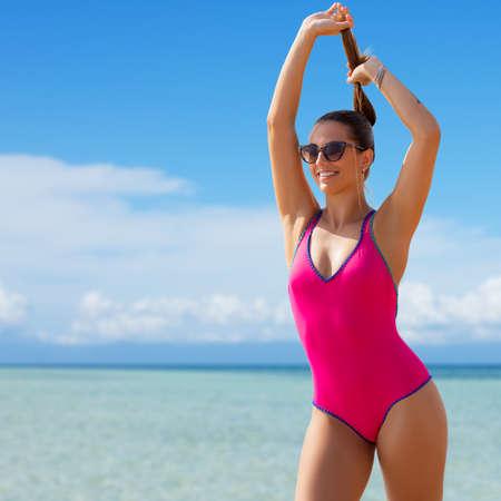 Close up portrait of stylish young woman wearing dark pink swimming costume on beach.