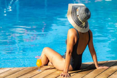 Close up rear view of woman in swimwear sitting at poolside. Girl wearing big sun hat with feet in water. Stok Fotoğraf - 154068918