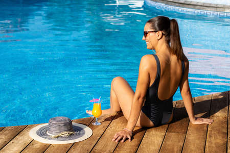 Close up rear view of attractive girl in swimwear sitting on wooden deck at outdoor poolside. Sunhat and fruit cocktail next to woman. Stok Fotoğraf - 154068925