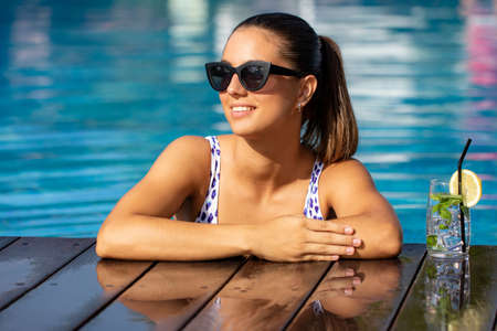 Close up portrait of attractive young woman in swimming pool next to cocktail. Stok Fotoğraf - 153919020