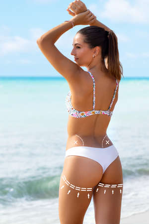Close up rear view portrait of young woman in white bikini showing perfect muscular buttock. Brunette standing on beach with conceptual surgical dotted contour lines. Stok Fotoğraf - 154068927
