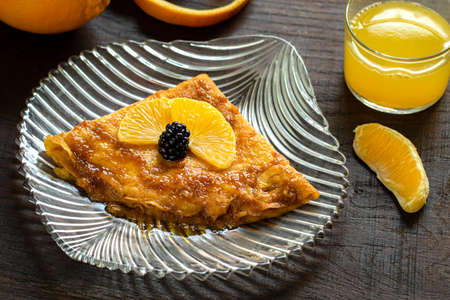 Close up sweet dessert of thin pancake with caramelized orange dressing. Homemade crepe suzette on transparent plate. Stok Fotoğraf - 155730966