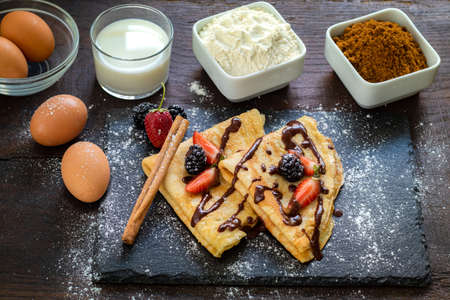 Top view of homemade thin pancakes surrounded with ingredients. Eggs, milk, flour  and sugar next to baked crepes on wooden table. Stok Fotoğraf - 155730951