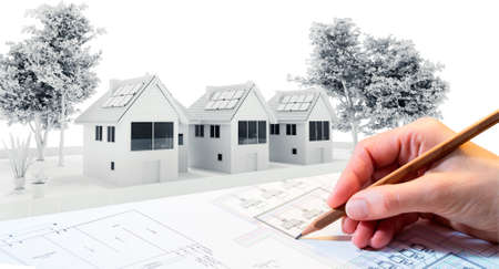 Close up of hand working on townhouse blueprints with 3D house model render in background.
