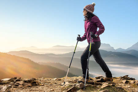 Full length portrait of female hiker walking on rocks with walking poles. Woman in winter sportswear against mountain background at sunrise.