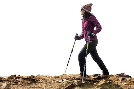 Close up side view portrait of young female hiker walking on rocks. Woman with walking poles isolated against white background. Stockfoto