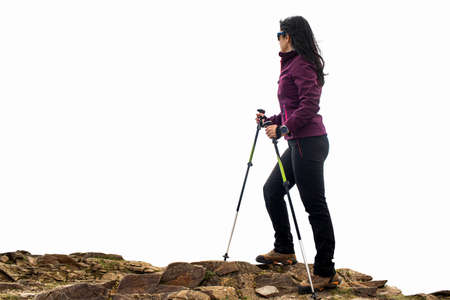 Close up rear view portrait of young female hiker in sportswear and walking poles. Woman standing on rocks isolated against white background.