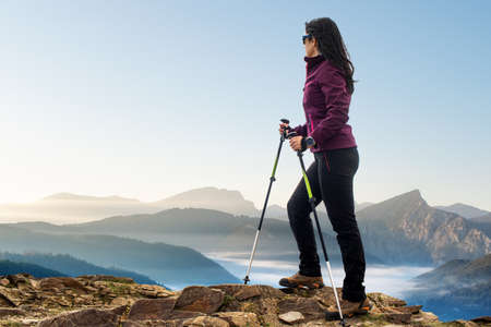 Close up rear view portrait of female hiker standing on rocky terrain with walking poles. Woman looking at mountains at sunrise.