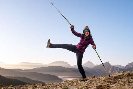 Fun portrait of young female hiker in mountains. Woman with walking poles jumping against mountain top silhouette background.