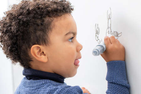 Close up portrait of little afro american boy drawing with marker pen on white board.