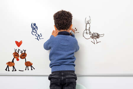 Medium close up rear view portrait of creative afro american kid drawing on white board. Boy creating childlike animals with marker pens.