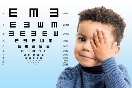 Close up face shot of little Afro American boy testing vision. Kid with closing on eye with hand. Vision chart with block letters in background.