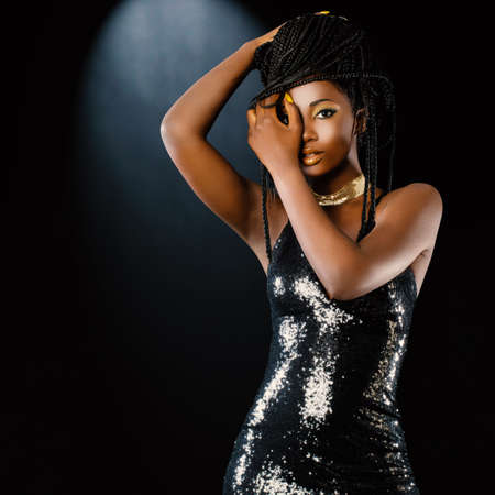 Close up studio portrait of young attractive african woman wearing party dress against dark background. Sexy girl playing with braids.