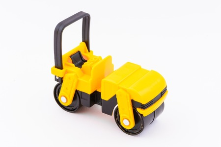 Isolated model of yellow steamroller on white background. Construction machine as a toy. Rolling using a machine.