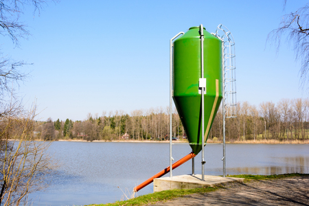 Fish feedstock on the shore of the pond. Full-strength silo. Feeding for fish.
