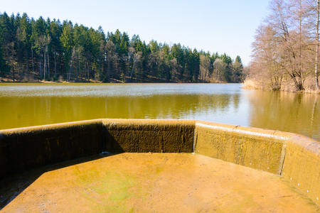 Water reservoir dike. Pond dam. Overflow of water in the lake.