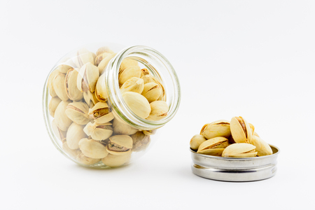 Isolated roasted and salted pistachios nuts on a white background. Healthy natural vitamins. Source of antioxidants and potassium. Pistachios in a glassful.