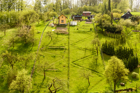 Cottage in a grassy hill. Chat area at the top of the hill. A cliche path to the cottages. Spring Outdoors Garden.