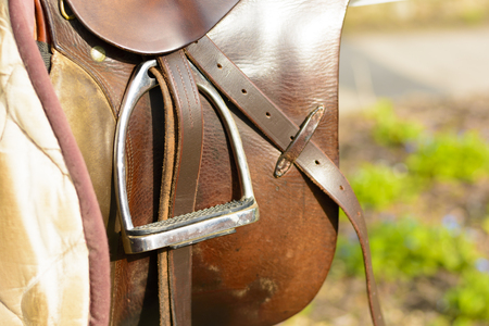 Closeup leather cowboy saddles hanging on the railing. Detail stirrup to the saddle. Removable saddles for horses in fresh air. Saddle hanging on a fence. Stock Photo