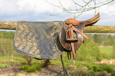 Leather cowboy saddle hanging on the railing. Removable saddle for horse in fresh air. Saddle hanging on a fence with a forest background. Stock Photo