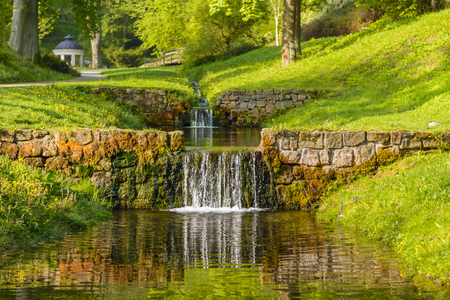 Small rock overflow to the stream in the park. Stream in the green valley at sunrise. Water cascade in the park.