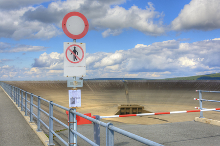 do not enter: Empty upper dam of the pumping hydroelectric power plant in the Czech Republic. View of the drained water reservoir. Pumping power station in repair. Do not enter.