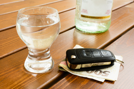 Do not drink when the drive. Car keys on a banknotes next to a glass of rum.. Alcohol is not behind the wheel
