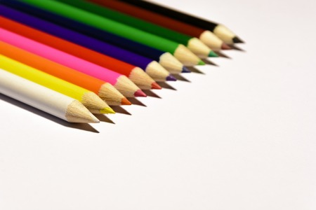 Colorful crayons on a white background. Drawing requirements