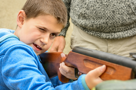 A little boy shooting from an air rifle to a target