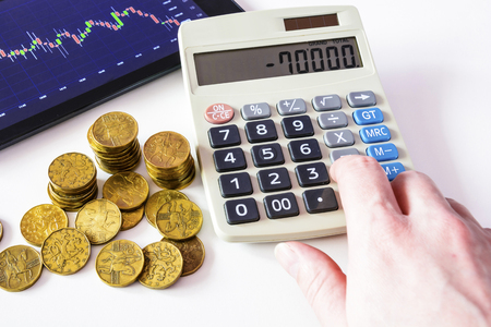 Gold coins and tablet placed on a white table showing a graph. Stock market trading. Calculation on Calculator. Watch the stock market on a tablet. Financial saving. Lots of Czech coins before the financial chart. Stock Photo