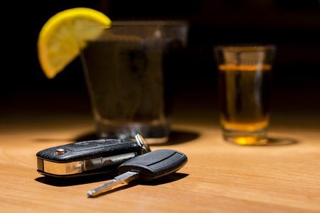 Car keys laid on the bar beside cocktail and whiskey. Whiskey and cocktail at the bar. Alcoholic glasses and car keys. Do not drink alcohol while driving.