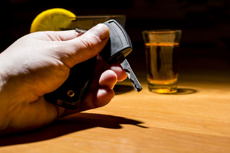 A man's hand holding car keys at a bar. Whiskey and cocktail at the bar. Alcoholic glasses and car keys. Do not drink alcohol while driving.