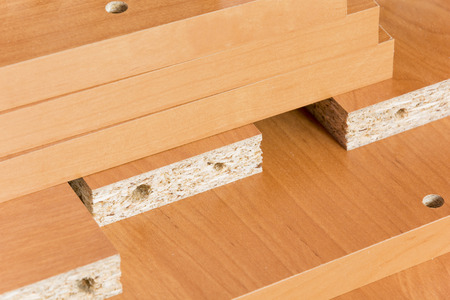 Wooden boards planked on the floor. Furniture material made of chipboard. Home assembling furniture. Фото со стока