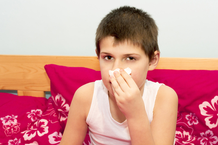 The boy stops bleeding from his nose with a handkerchief. The flu season. Influenza epidemic in the Czech Republic. Nose injury with bleeding. Stock Photo