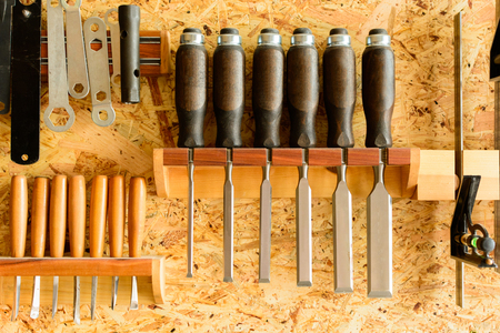 Carving tools hanging on the wall holder. The chisels aligned in the holder. View of the wall with tools. Banque d'images