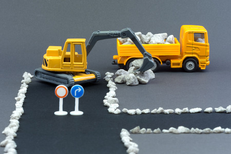 Diorama road construction with yellow construction machinery models. Construction concept. Children's toys of construction machinery. Closed road with no entry. Excavator loads stones on truck. 免版税图像