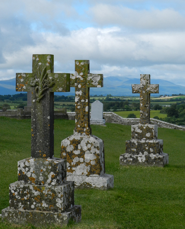 Three celtic crosses at Rock of Cashel with mountains in the background Archivio Fotografico - 121635074