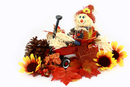 Autumn Scarecrow Series Red Wagon, Flowers, And Leaves  Stock Photo