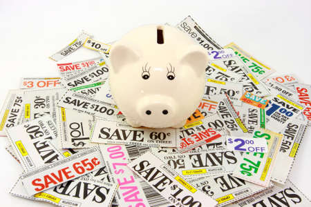 Piggy Bank On Pile Of Money Saving Grocery Coupons  photo
