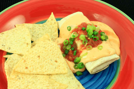 smothered: Crispy Burrito Smothered With Cheese Sauce And Salsa Stock Photo