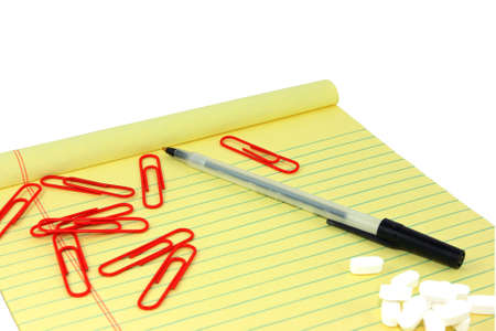 legal pad: Yellow Legal Pad With Paperclips, Pen, And White Pills  Stock Photo