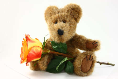 Small Teddy Bear Holding An Orange And Yellow Rose