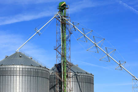 Metal Grain Bins Against A Blue Sky Stock Photo