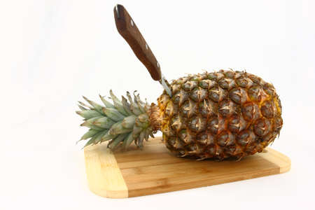 Fresh Pineapple On Cutting Board With Knife photo