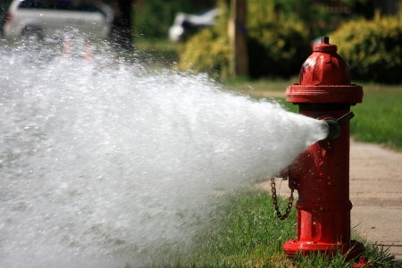 A red fire hydrant left open to gush a high pressure stream of water into a residential neighborhood  Stock Photo - 14542579