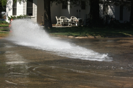 An open fire hydrant beginning to flood the streets of a quiet residential neighborhood