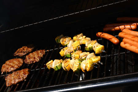 Hamburgers, hotdogs, and vegetable kabobs cooking on an outdoor gas grill in the summer sun.