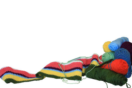 thread count: Colorful skeins of yarn and the beginning of a striped crocheted blanket isolated on a white background. Stock Photo